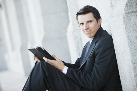 Caucasian businessman using digital tablet outdoors