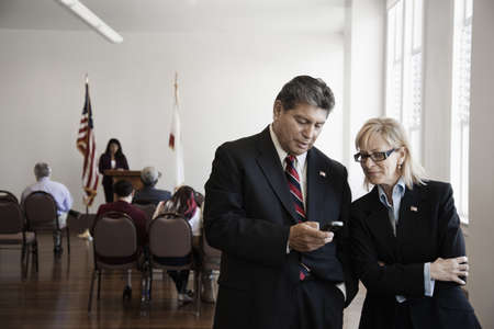 Hispanic businessman text messaging on cell phone