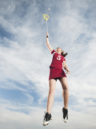 Caucasian teenager in mid-air playing lacrosse