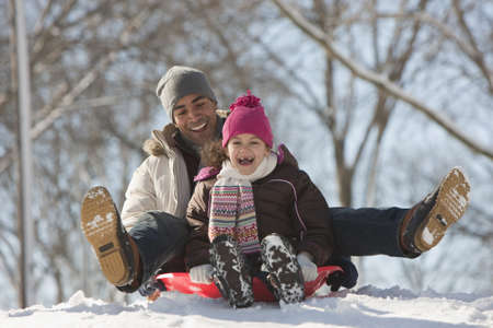 Father and daughter sledding on snow covered hill LANG_EVOIMAGES