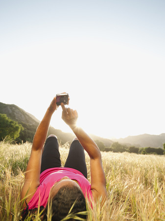 Black woman laying in field using cell phone LANG_EVOIMAGES
