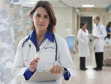 Hispanic doctor holding medical record LANG_EVOIMAGES