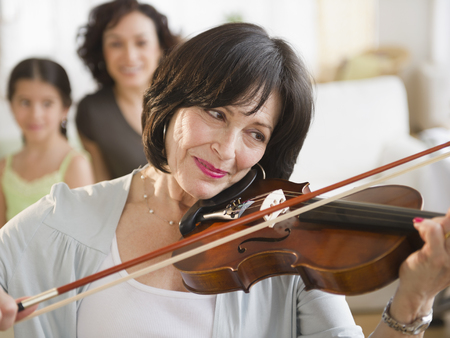 Mother and daughter watching grandmother playing violin