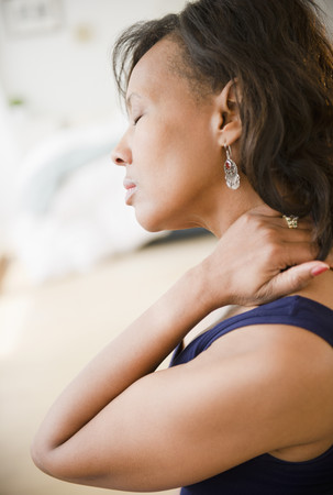Black woman rubbing her neck LANG_EVOIMAGES