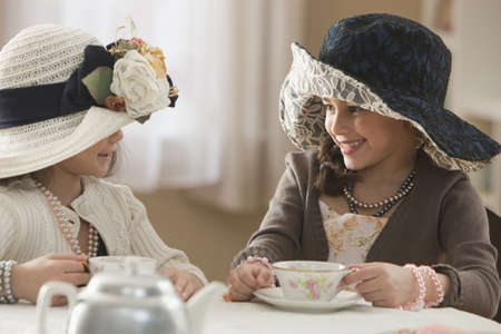 Girls dressed up having tea party LANG_EVOIMAGES