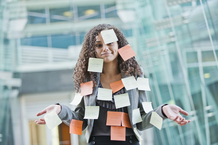 Caucasian businesswoman covered in sticky notes LANG_EVOIMAGES
