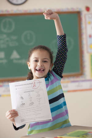 Excited Hispanic girl holding test with an A+