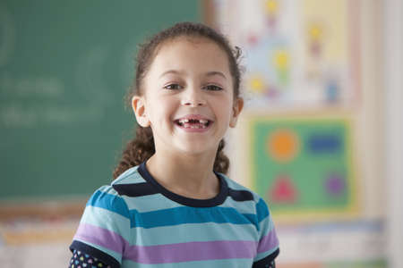 Hispanic girl in classroom missing a tooth