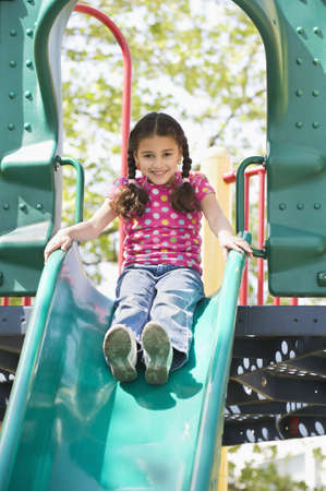 Hispanic girl sliding down slide on playground