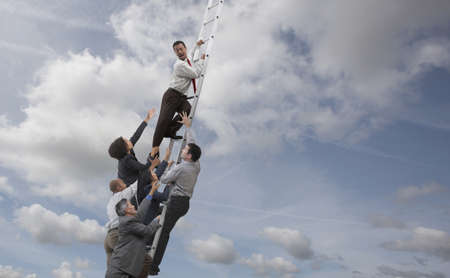 Business people chasing co-worker up ladder into clouds LANG_EVOIMAGES