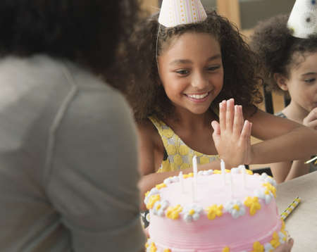 Mixed race mother bringing daughter a birthday cake LANG_EVOIMAGES