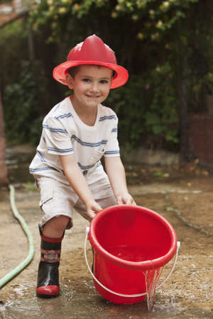 Caucasian boy playing with bucket wearing firemans hat LANG_EVOIMAGES