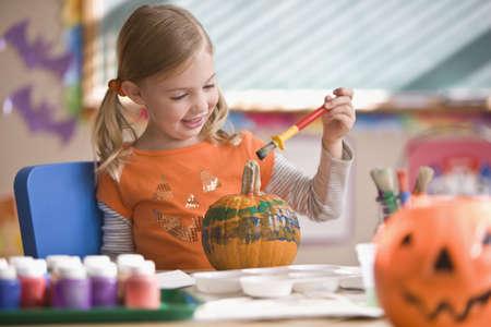 Caucasian girl painting pumpkin LANG_EVOIMAGES