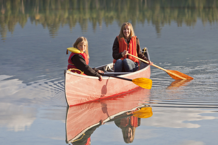 Caucasian mother and daughter canoeing on Lake Edith