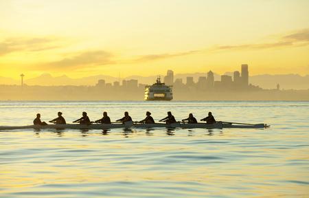 Team rowing boat in bay