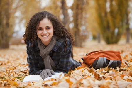Caucasian woman laying in autumn leaves reading book