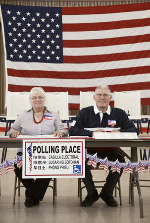 Caucasian man and woman working at polling place LANG_EVOIMAGES
