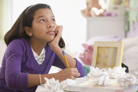 Bored Hispanic student doing homework LANG_EVOIMAGES