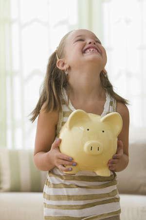 Grinning girl holding piggy bank