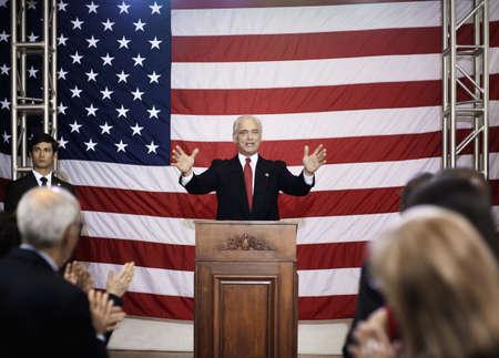 Caucasian politician making speech at podium LANG_EVOIMAGES