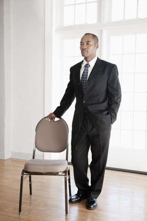Mixed race businessman standing near chair LANG_EVOIMAGES
