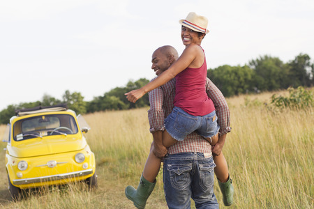 Man piggybacking wife in field near car LANG_EVOIMAGES