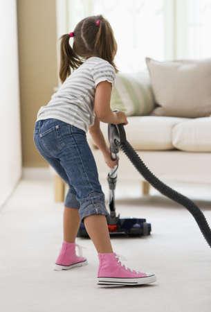 Girl vacuuming living room floor LANG_EVOIMAGES