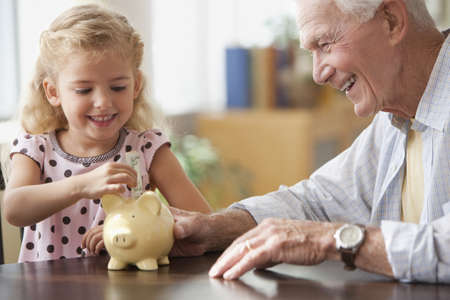 Caucasian grandfather watching granddaughter putting coin into piggy bank LANG_EVOIMAGES