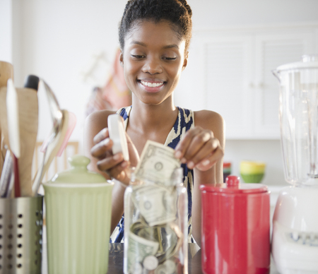 Black woman taking money out of jar LANG_EVOIMAGES