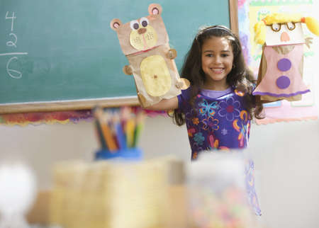 Hispanic girl holding sack puppets in classroom LANG_EVOIMAGES