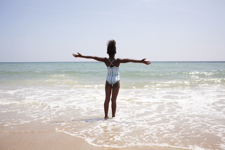 Jamaican girl wading on beach LANG_EVOIMAGES