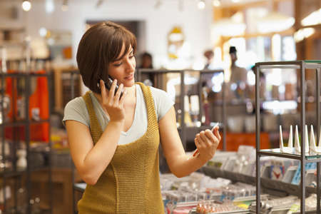 Hispanic woman working in store and talking on cell phone
