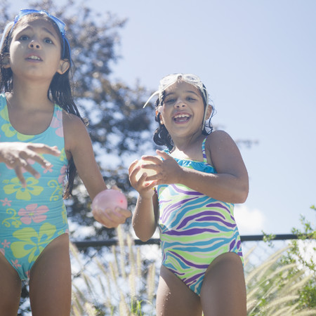 Hispanic girls in bathing suits playing with water balloons LANG_EVOIMAGES