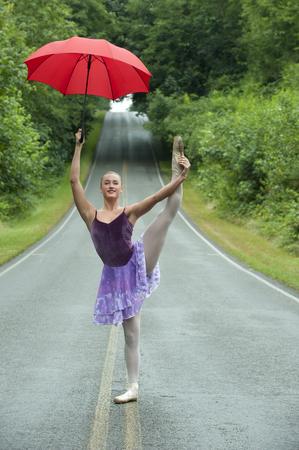 Caucasian ballerina dancing on remote road with umbrella