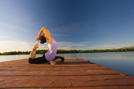 Korean woman practicing yoga on lake pier