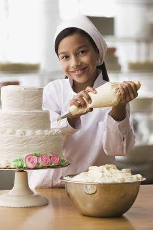 Hispanic girl icing wedding cake