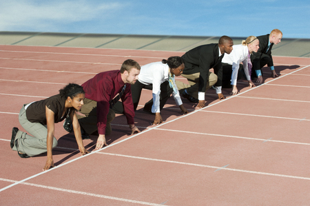 Business people crouching at starting line on track