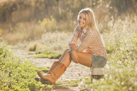 Caucasian woman sitting on tackle box in field