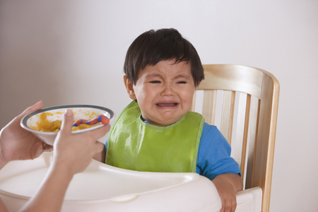 Hispanic mother trying to feed crying baby boy LANG_EVOIMAGES