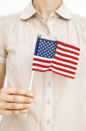 Woman holding repaired American flag LANG_EVOIMAGES
