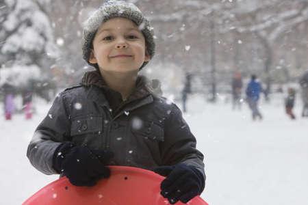 Caucasian boy sledding in snow LANG_EVOIMAGES