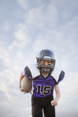Mixed race football player running with football LANG_EVOIMAGES