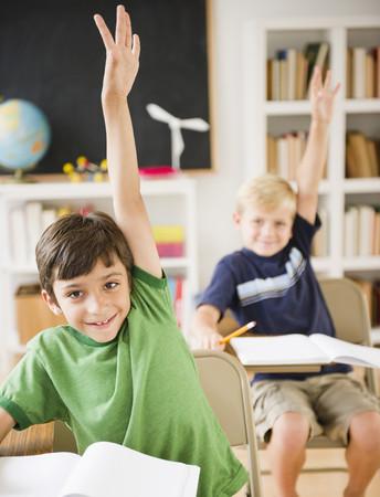 Chlapci v učebně zvedají ruce