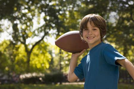 Caucasian boy throwing football LANG_EVOIMAGES