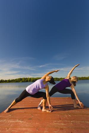 Women stretching on lake pier LANG_EVOIMAGES