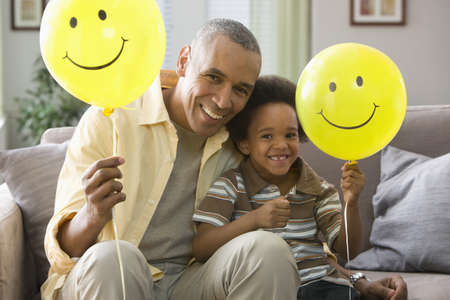 Grandfather and grandson holding balloons with smiley faces LANG_EVOIMAGES