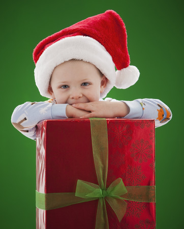 Caucasian boy in Santa hat leaning on Christmas gift LANG_EVOIMAGES