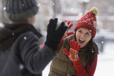 Caucasian boy throwing snowball at mother