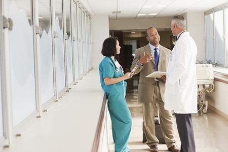 Doctors and drug salesman talking in hospital LANG_EVOIMAGES