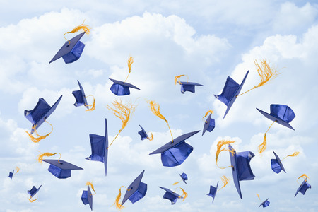Graduation mortarboards being thrown in the air